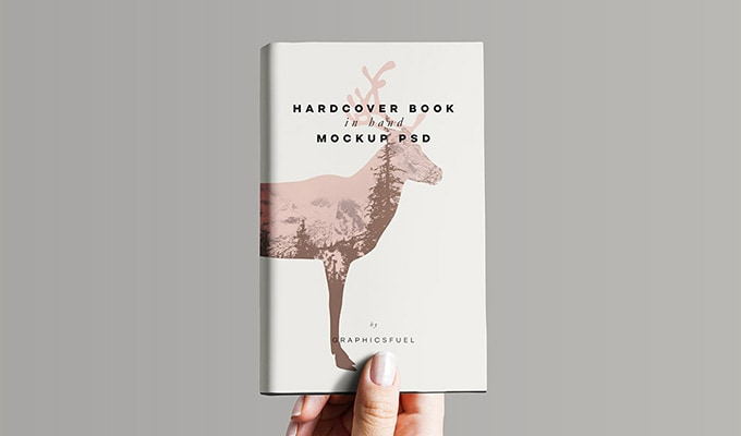 hardcover book being held by a women's hand PSD book cover mockup template